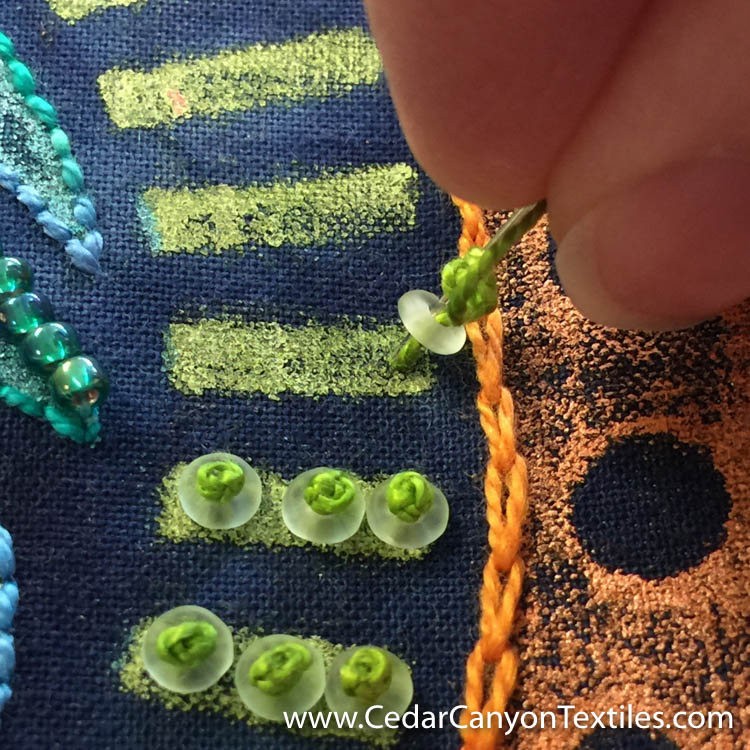 3. Insert the needle through the O Bead and into the fabric.